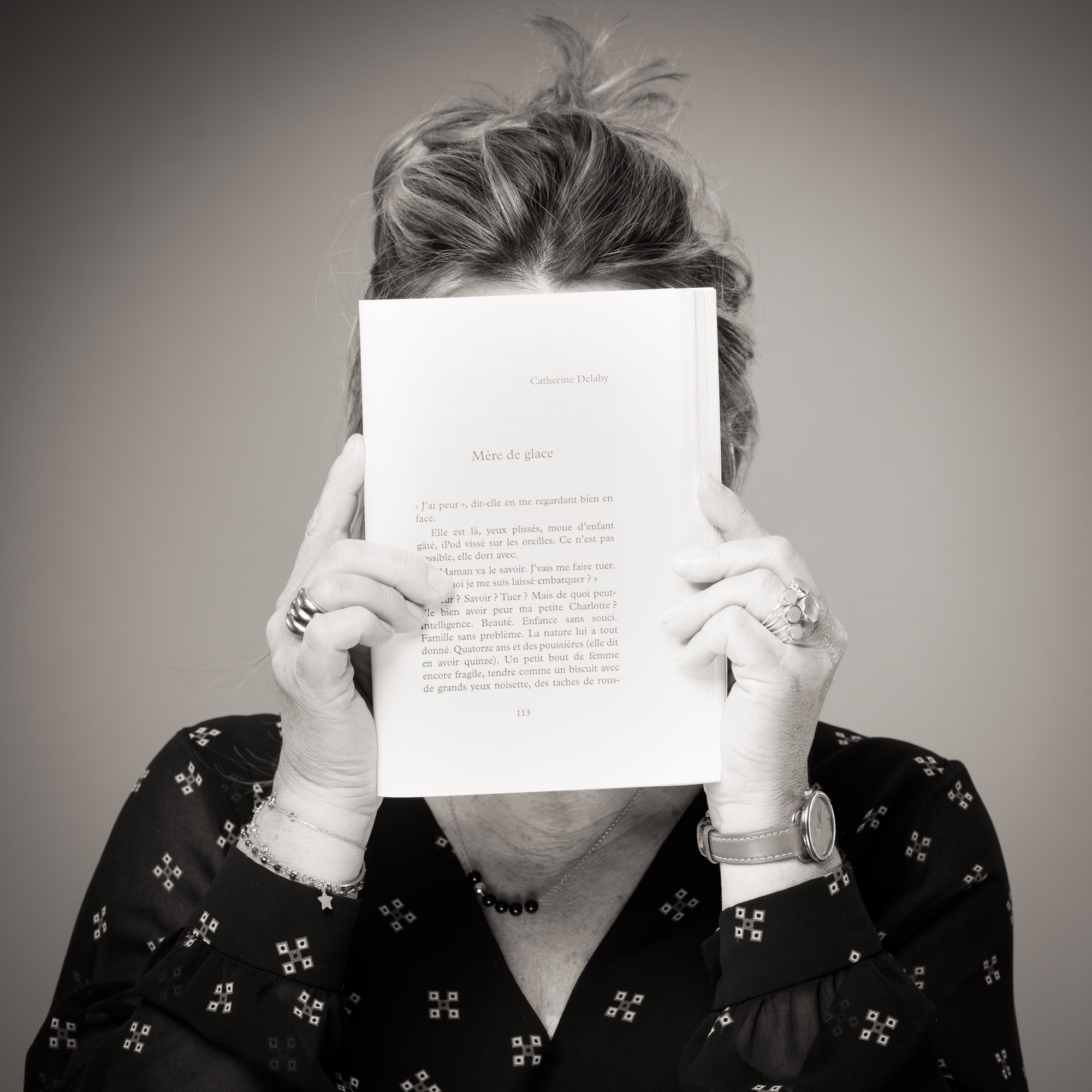 Catherine Delaby se cachant le visage avec un livre