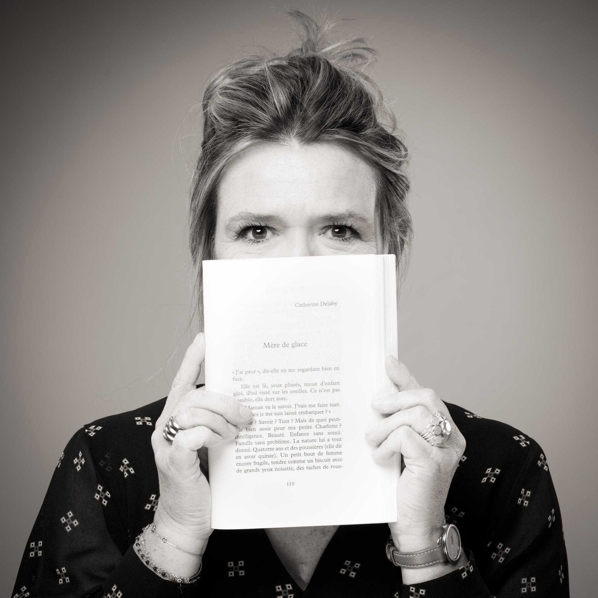 Catherine Delaby se cachant la moitié du visage avec un livre