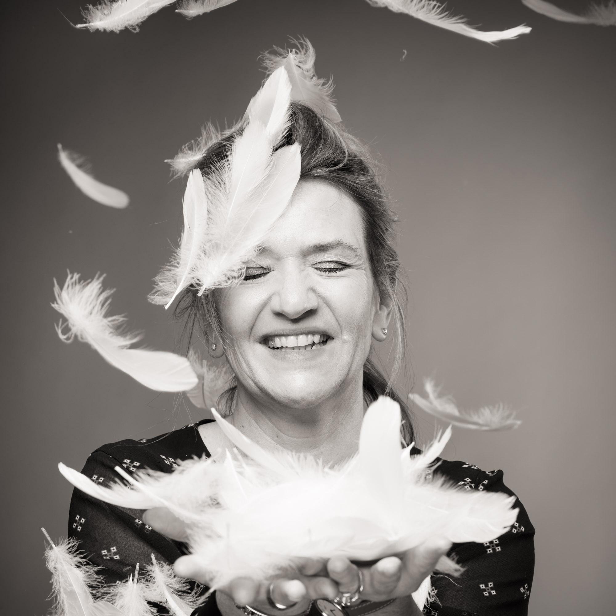 Catherine Delaby tout sourire avec des plumes blanches qui volent
